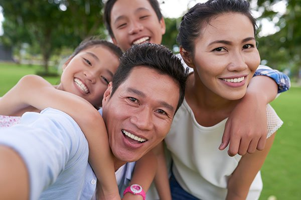 A family smiling into camera taking a selfie outside.