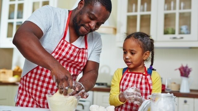 A dad helps his daughter cook in the kitchen