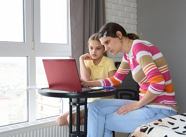 Mom and daughter watch school on computer.