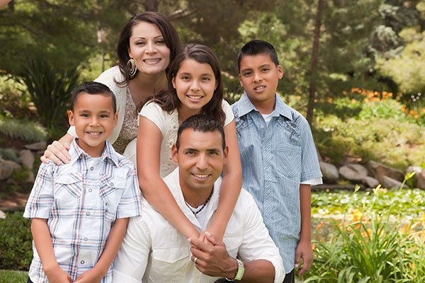 An outside picture of a smiling family.