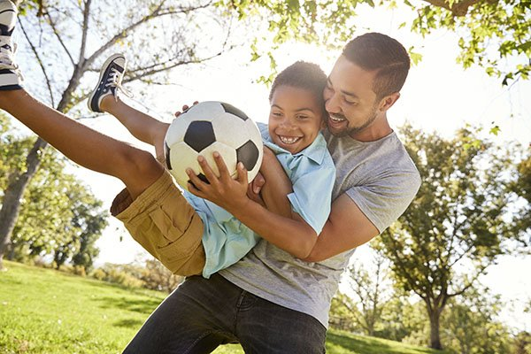 A father hugging his son as they play soccer