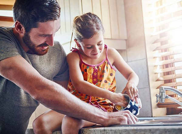 A dad teaches his young daughter to wash dishes.