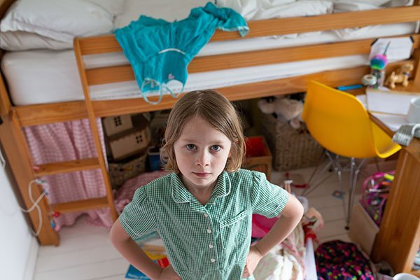 A young girl standing in her messy room.